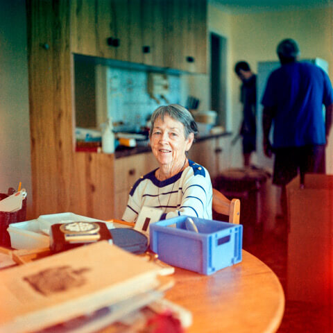 An older woman sits at the kitchen table, while two men move a fridge in the background.